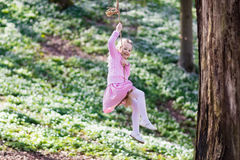 Child swinging on tree rope swing Stock Photos