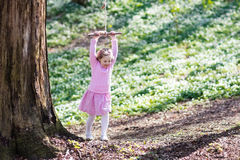 Child swinging on tree rope swing Royalty Free Stock Image