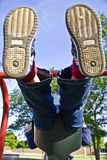 Child on swings. Child swinging high on swing set at a playground Royalty Free Stock Photos