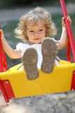 Child on swings. Cute little girl on swings royalty free stock images