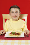 Child at table with plate of food stock images