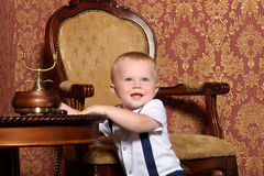 Child at the table in the vintage interior. Reaches for the phone Royalty Free Stock Photography