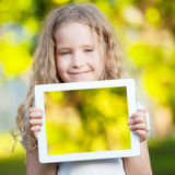 Child with tablet computer. On meadow. Girl showing screen pc Stock Image