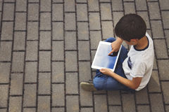 Child with tablet computer sitting on the pavement outdoors. Stock Photos