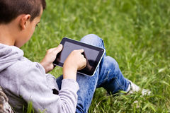 Child with tablet. Child in the park with tablet in hands Stock Photo