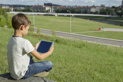 Child with tablet pc outdoors. Boy on grass holds computer. Back view. Technology people education concept. Child with tablet pc outdoors. Boy on grass with stock images