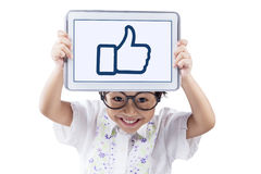 Child with tablet showing a thumb up sign Stock Photo