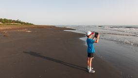 A child with a tablet takes pictures of the sea stock photo