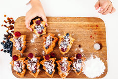 Child take berry cake from board, flat lay Stock Image