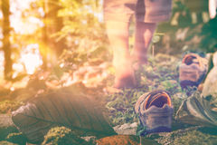 Child take off leather shoes, child's foot learns to walk on grass with bright sunlight, reflexology massage. Kid relax in park on vacation. Shallow depth of royalty free stock photography