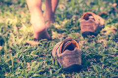Child take off shoes. Child's foot learns to walk on grass. Child take off leather shoes. Close up child's foot learns to walk on grass, reflexology massage. Kid Stock Image