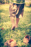 Child take off shoes. Child's foot learns to walk on grass Royalty Free Stock Photo