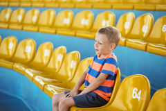 Child take own seat in the stadium or dolphinarium and waiting p. Little boy sitting in an empty stadium among yellow plastic numbered seats and applauds. Child stock image