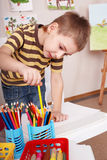 Child take pencil in play room. Royalty Free Stock Image