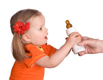 Child take  small bottle with milk and dummy Stock Image