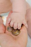Child takes coins. The child takes the hand coins Royalty Free Stock Photo