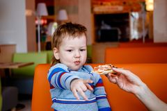 The child takes a slice of pizza stock image