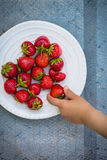 The child takes a strawberry Royalty Free Stock Photography