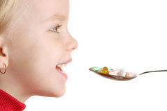 Child takes vitamins by spoon. Isolated in white Stock Photography