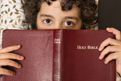 Child taking a break from reading the holy bible at home Royalty Free Stock Image