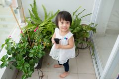 Child taking care of plants. Cute little girl watering first spr Royalty Free Stock Image