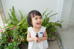 Child taking care of plants. Cute little girl watering first spr Stock Photos
