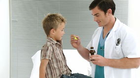 Child taking cough medicine in medical office Stock Photography