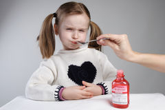 Child taking medication. Unhappy little girl taking medication Stock Photo