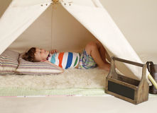 Child taking a nap in a teepee tent Royalty Free Stock Photos