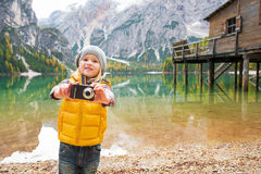 Child taking photo while on lake braies, italy Stock Image