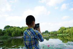 A child is concentrated on taking photoes Stock Photo