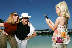 Child taking a picture. A view of a young girl taking a photo of two woman on a cellphone camera at the shore Stock Images