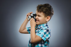 Child taking a picture using a retro rangefinder camera isolated grey background Royalty Free Stock Photo