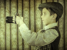 Child taking pictures with vintage camera Royalty Free Stock Image