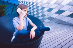 Child talking on cell phone in the street Stock Photography