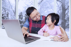 Child talking with dad while studying at home Stock Image