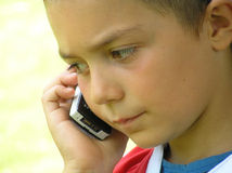 Child talking in mobile phone. Looking like a question mark royalty free stock photography