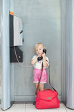 Child talking the phone in the airport Royalty Free Stock Photography