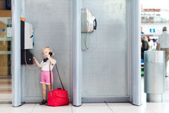 Child talking the phone in the airport Royalty Free Stock Image