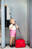 Child talking the phone in the airport Royalty Free Stock Images