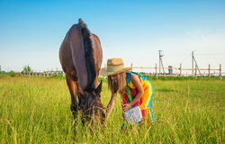 The child talks to the horse. Little cute girl in cowboy hat with horse on lawn Stock Photos