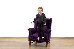 Child tantrums angry screaming on an armchair. Isolated on white background Stock Photo