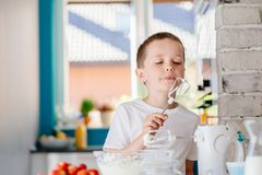Child tasting pastry from mixer agitator Stock Image