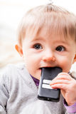 Child tasting a remote control to check Stock Photo