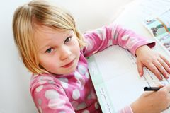 Child teach. A blonde girl 6 years old teach writing royalty free stock photo