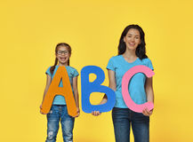 Child and teacher with big letters Stock Photo