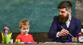 Child and teacher on busy face painting, drawing. Art lesson concept. Teacher with beard, father teaches little son to. Draw in classroom, chalkboard on stock photos
