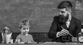 Child and teacher on busy face painting, drawing. Art lesson concept. Teacher with beard, father teaches little son to. Draw in classroom, chalkboard on stock image