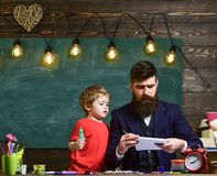 Child and teacher on busy face painting, drawing. Art lesson concept. Talented artist spend time with son. Teacher with. Beard, father teaches little son to stock image