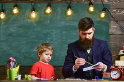 Child and teacher on busy face painting, drawing. Arts lesson concept. Teacher with beard, father drawing while little. Son hang out near, in classroom stock image